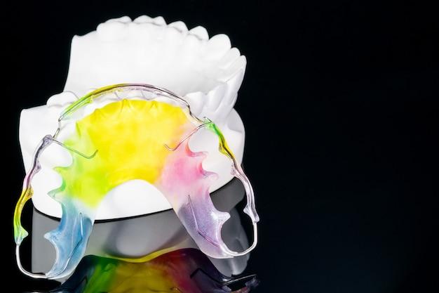 De cerca; dispositivo de ortodoncia retenedor dental y herramientas dentales de color negro.