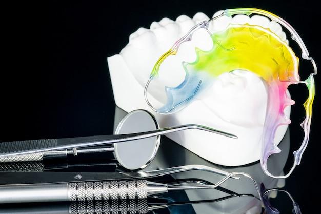 De cerca; dispositivo de ortodoncia retenedor dental y herramientas dentales sobre el fondo negro.