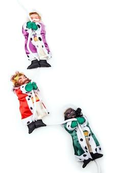 Cerca de divertidos muñecos de navidad de tres reyes magos en blanco