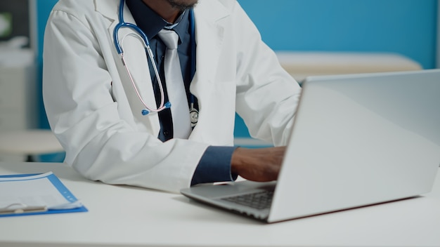 Cerca del doctor escribiendo en el teclado de la computadora portátil en el gabinete médico