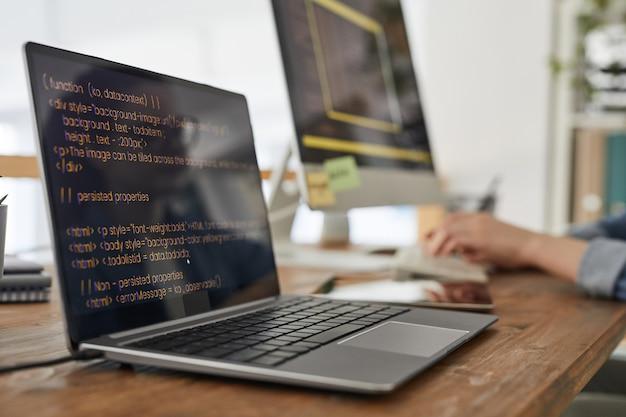 Cerca de dos computadoras con código de programación en pantalla en el interior mínimo de la oficina en casa con las manos escribiendo en segundo plano, espacio de copia