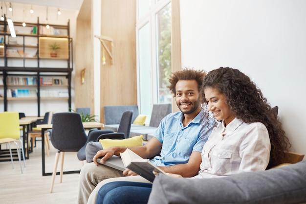 Cerca de dos jóvenes en ropa casual sentado en el sofá en la biblioteca moderna. chica leyendo para reservar, preparándose para la conferencia universitaria. guy cara feliz expresión