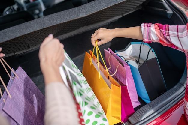 Cerca de dos pares de manos sacando bolsas de la compra del maletero del coche