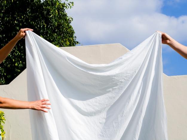 Cerca de dos personas colgando una sábana blanca en la línea