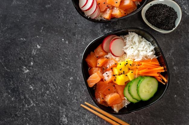 Cerca de dos poke bowls con salmón y verduras