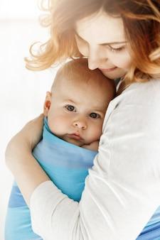 Cerca del dulce bebé con sus grandes ojos grises. mamá acurruca a su hijo con ternura y amor. concepto de familia