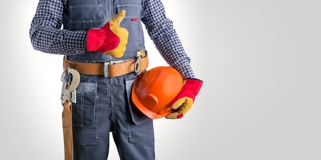 Cerca de electricista en uniforme sosteniendo casco, mostrando el pulgar hacia arriba sobre fondo blanco.