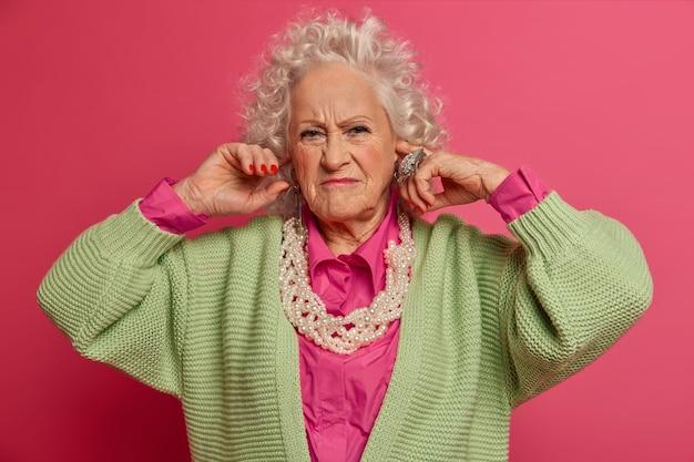 Cerca de elegante anciana con ropa elegante aislada
