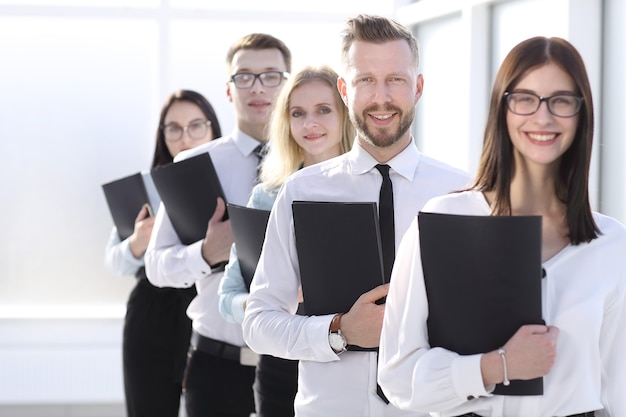 De cerca. empleados con carpetas de archivos en fila. negocios y educación