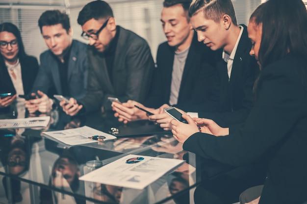 De cerca . empleados que utilizan sus teléfonos inteligentes para trabajar con datos financieros.