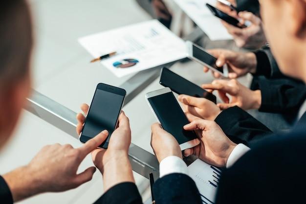 De cerca . empleados con teléfonos inteligentes analizando datos financieros. personas y tecnologia