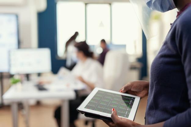 Cerca de la empresaria africana comprobación de gráfico de estadísticas en tablet pc
