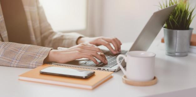 Cerca de empresaria escribiendo en la computadora portátil