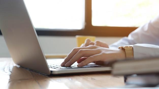Cerca de la empresaria o contador mano sujetando la pluma trabajando en una computadora portátil para calcular datos comerciales