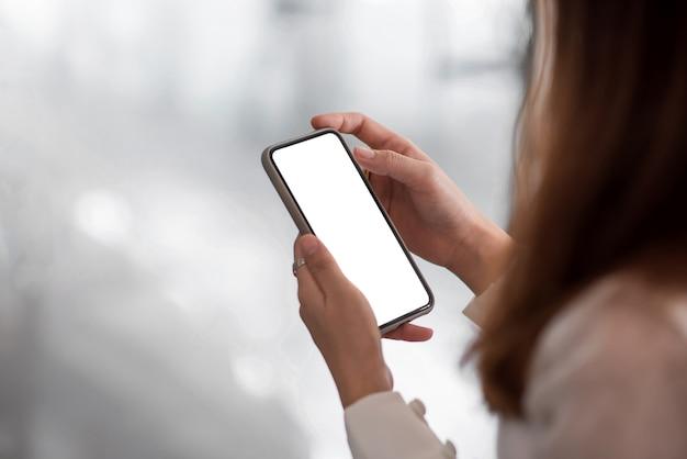 Cerca de la empresaria de pie mediante teléfono móvil en pantalla blanca