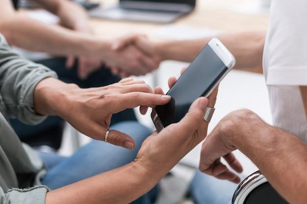 De cerca. empresaria utiliza un teléfono inteligente sentado en la oficina. personas y tecnologia