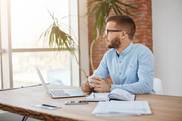 Cerca del empresario adulto sentado en la oficina mirando a un lado con expresión pensativa