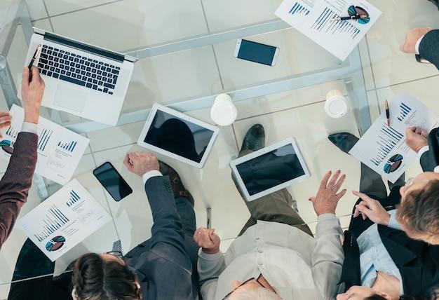 De cerca. empresario con empleados discutiendo el informe financiero.