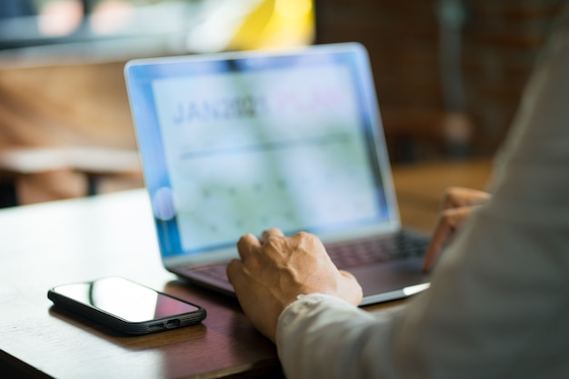 Cerca de un empresario mirando el planificador de año nuevo 2021 en la pantalla del portátil para planificar su negocio para el próximo año nuevo.