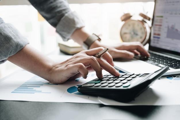 Cerca del empresario o contador mano que sostiene la pluma trabajando en la calculadora para calcular los datos comerciales