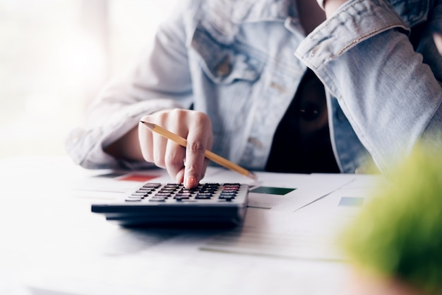 Cerca del empresario o contador mano sujetando lápiz trabajando en calculadora