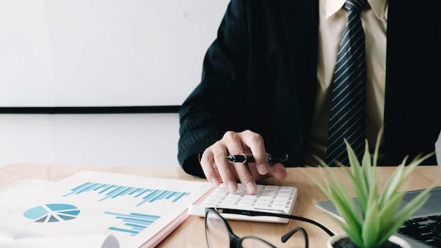 Cerca del empresario o contador mano sujetando la pluma trabajando en la calculadora para calcular datos comerciales
