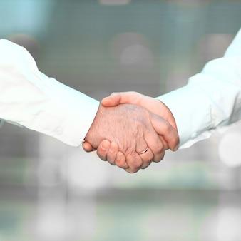 De cerca. empresarios de apretón de manos en el fondo borroso. el concepto de asociación
