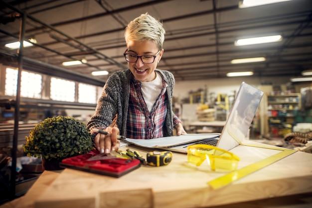 Cerca de encantadora ingeniera de cabello corto con anteojos sosteniendo triángulo mientras trabajaba con planos y computadora portátil en el taller