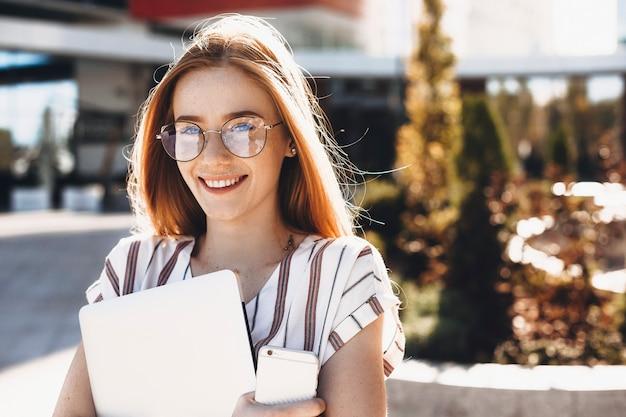 Cerca de una encantadora joven autónoma sosteniendo una computadora portátil y un teléfono inteligente mirando a la cámara riendo contra un edificio.