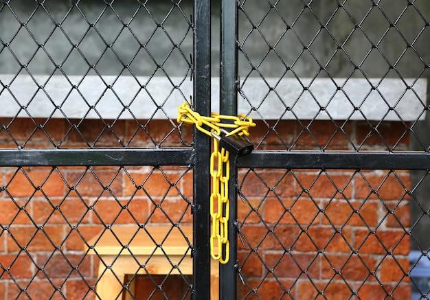 Cerca de enlace de cadena amarilla y puerta de metal con cerradura
