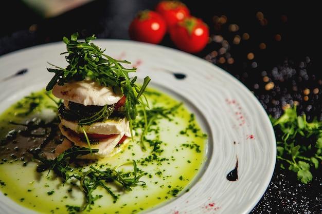 Cerca de ensalada de carpese en capas con mozzarella y tomate y rúcula