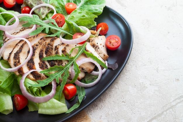Cerca de ensalada saludable con pollo a la parrilla, cebollas y tomates. comida sana.