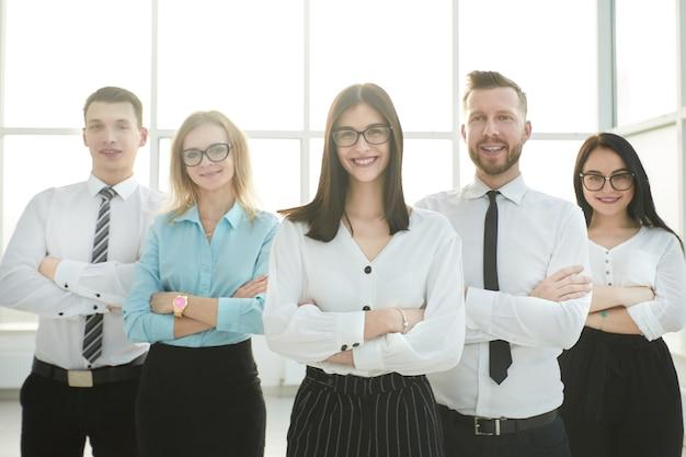 De cerca. equipo de negocios confiado en el fondo de una oficina luminosa.