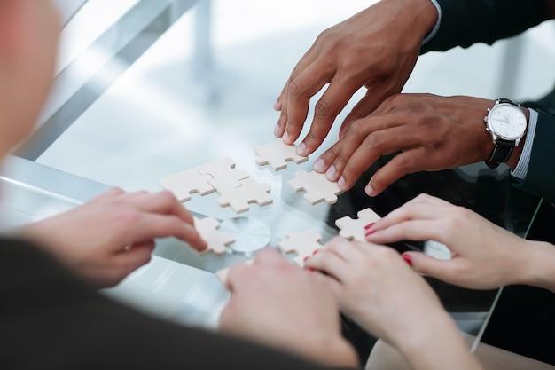 De cerca. equipo de negocios ensamblar piezas de rompecabezas concepto de soluciones empresariales.