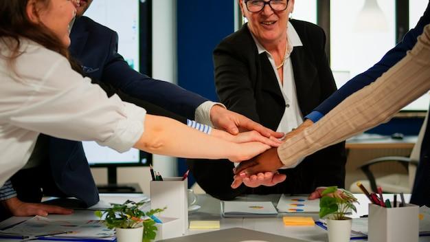 Cerca del equipo de negocios multiétnico creativo feliz celebrando el proyecto exitoso, recibiendo buenas noticias. diversos colegas con una nueva oportunidad disfrutando de la reunión de la victoria en la oficina de la sala amplia.