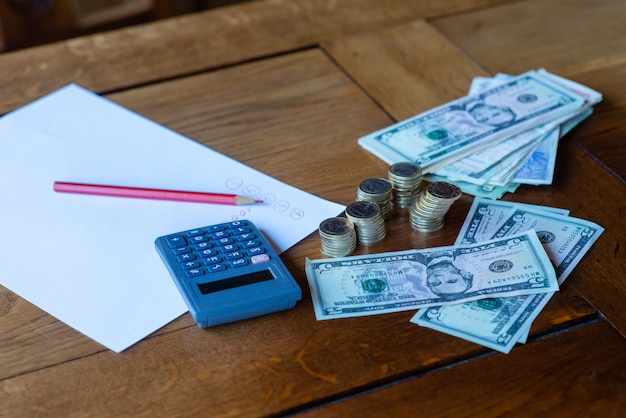 Cerca del escritorio de oficina con calculadora, documentos y dinero