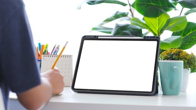Cerca de la escritura a mano del hombre y la tableta digital con fondo de mesa de trabajo de pantalla en blanco para maqueta, plantilla