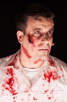 Cerca de espeluznante zombie cubierto de sangre sobre fondo negro. maquillaje creativo.