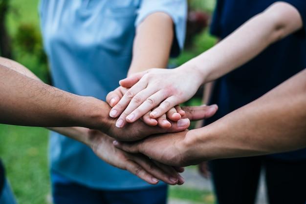 Cerca de los estudiantes del equipo de trabajo en equipo pila de manos juntas. inicio, concepto de éxito.