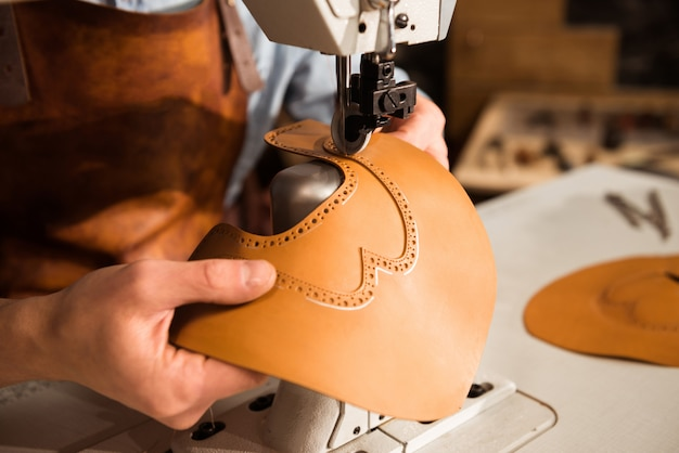 Cerca de un fabricante de botas trabajando con cuero textil