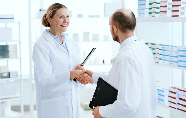 De cerca. farmacéutica saluda a un colega con un apretón de manos.