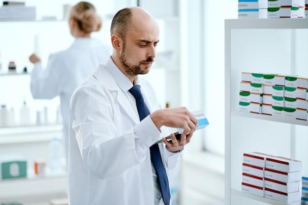 De cerca. farmacéutico con una tableta digital está eligiendo un medicamento para cumplir con un pedido en línea.