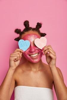 Cerca de feliz mujer étnica disfruta aplicando mascarilla aislada