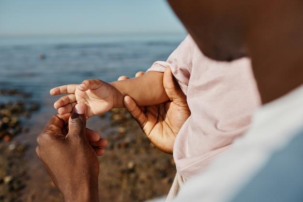 Cerca de feliz padre afroamericano sosteniendo una mano pequeña y jugando con el espacio de copia del hijo del bebé