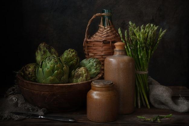 De cerca la foto de la alcachofa fresca en el viejo cuenco de madera y manojo de espárragos verdes. naturaleza muerta sobre fondo oscuro.