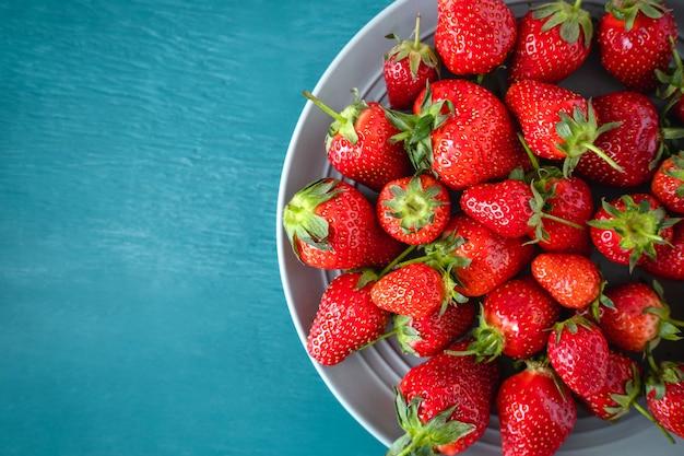 Cerca de una fresa fresca en un recipiente sobre fondo azul claro