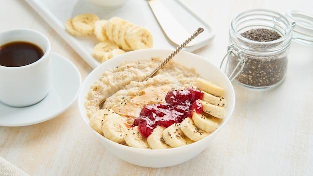 Cerca de gachas de avena, desayuno de dieta vegana saludable con mermelada de fresa, mantequilla de maní,