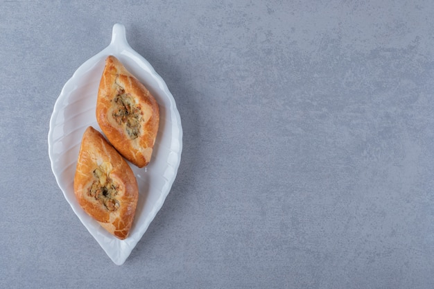 Cerca de galletas caseras frescas en placa blanca sobre superficie gris