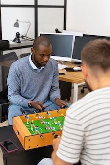 De cerca a la gente que se divierte jugando al fútbol de mesa