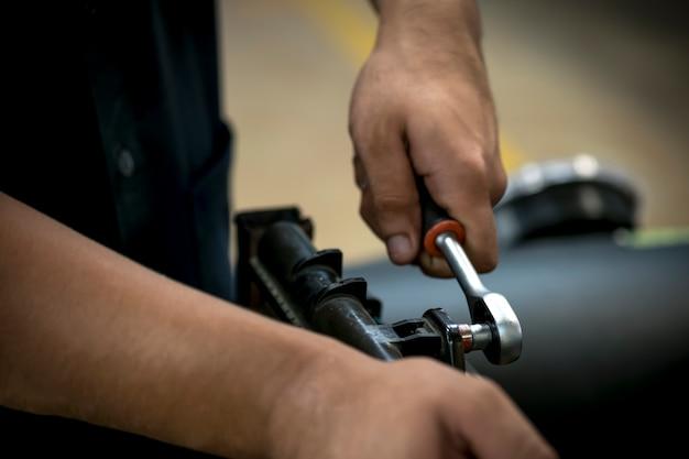De cerca, la gente está reparando un auto. use una llave y un destornillador para trabajar.